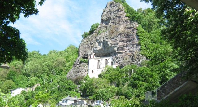 a vertical rock face amongst trees with a white church built deep into the rock