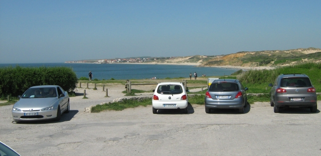 inf the foreground cars on a gravel carpark overlooking a long curving sandy shoreline with dunes
