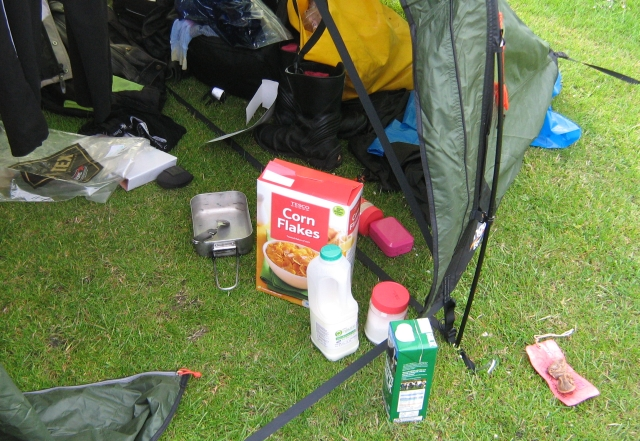 cornflakes box, billy can and general camping stuff in the tent entrance