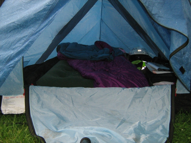 inside a small blue tent filled with airbed, sleepingbag, bags and motorcycle gear