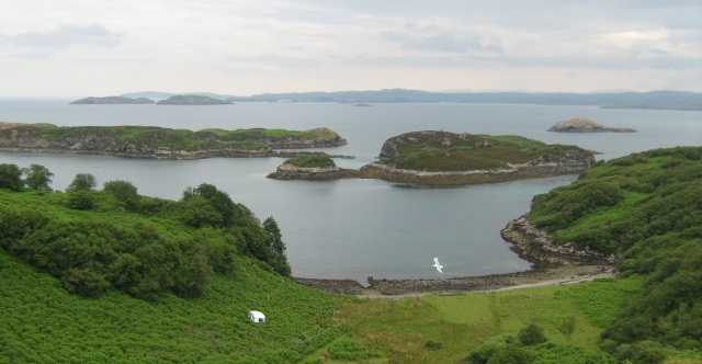 the view from drumbeg viewpoint.  islands in the sea and a steep hill to the shore, and a caravan in the bushes
