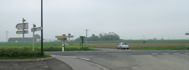 broad flat farmland with a crossroad and signs in france