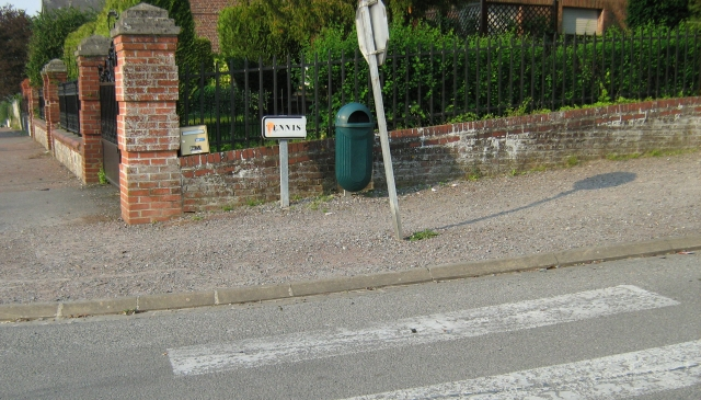 gravel footpath, faded pedestrian crossing markings and a signpost leaning a little in france