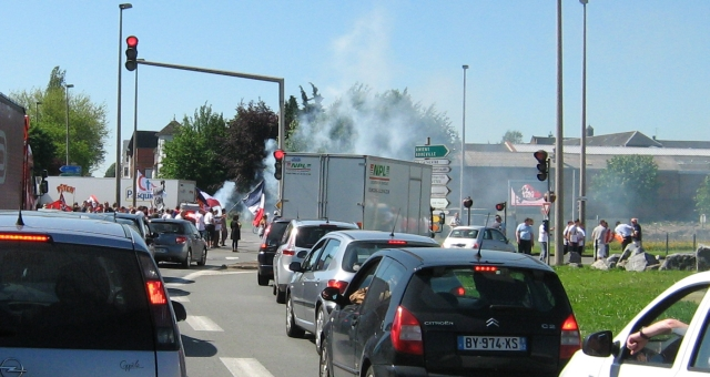 lines of traffic in the distance protestors with smoking flares and banners in arras