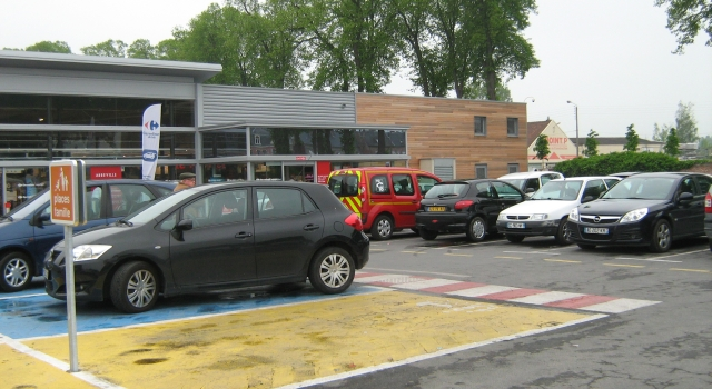 a car park with cars outside a french supermarket