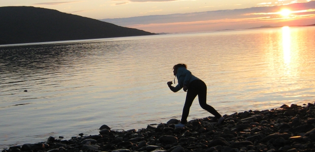 Sharon skimming stones at ullapool in a glorious sunset