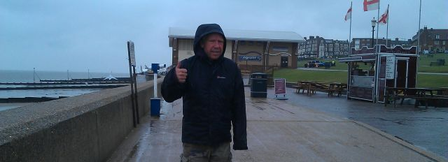 a man wearing a big rain coat looking very cold and wet on the sea front, giving the thumbs up
