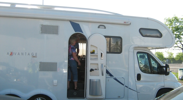 a large white campervan in the sunshine with a lady stood in the doorway