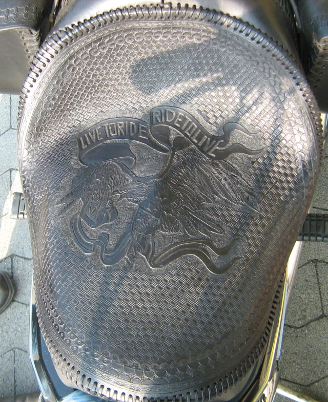 a motorcycle seat with fine detailed leatherwork showing an eagle and live to ride