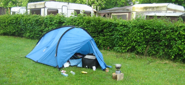 my small tent on a strip of grass with 2 dirty mouldy caravans in the background at the campsite in lebach