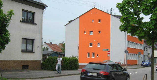 a bright orange apartment block with a gentleman walking in front
