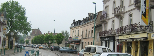 a french street with a few shops and the boulangerie in the rain looking grey and miserable
