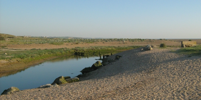 a small river winding past through the saned dunes with a town in the far distance