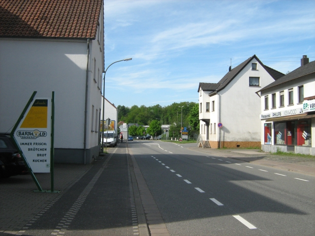 a broad street in a german town with a sign in the foreground for the bakery