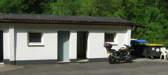 a white small toilet and shower block with my bike in front of it at the campsite in cocham