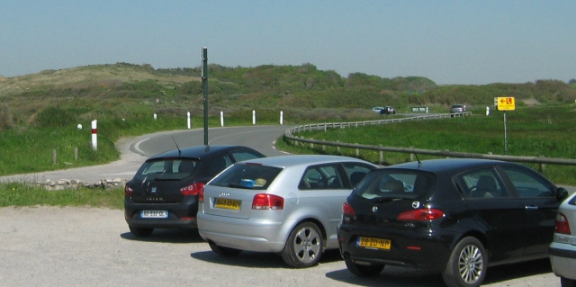 a corner of a road among dunes with cars in a car park in the foreground