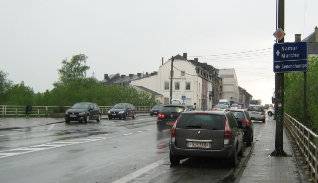 a wet street in bastogne with wet cars and houses