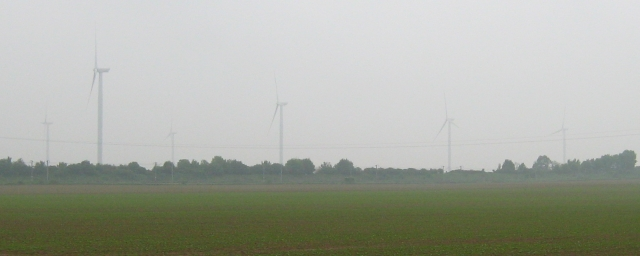 4 wind turbines in the misty distance on flat french farmland