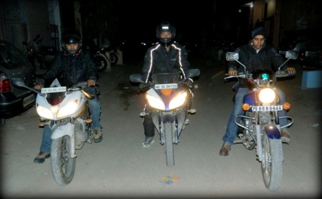 3 indian motorcyclists side by side riding through a dark street