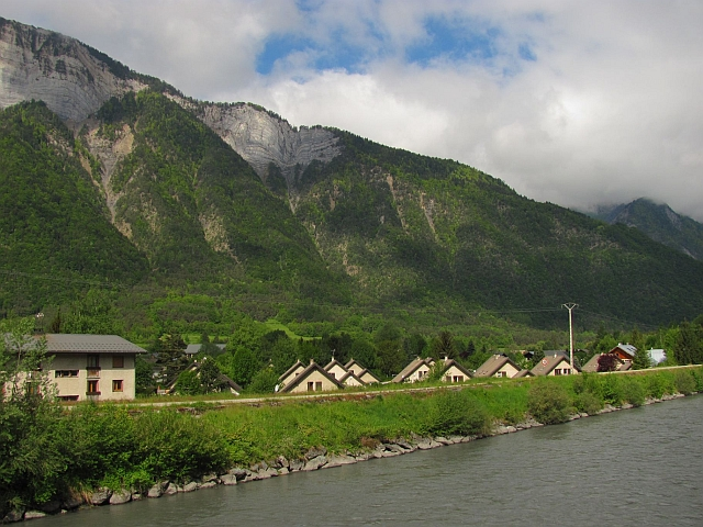 romanche river and valley floor, mountains to the side, lush green trees and alpine houses at le bourg d'oisans