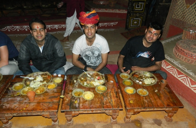 arjun and friends at on the floor eating a very hearty meal