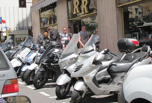 a line of scooters parked at the roadside in the cramped streets and traffic in monaco