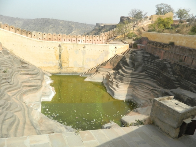 a pond in the base of sculptured steps and ridges in an indian palace