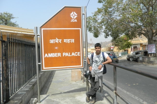 a motorcyclist posing by the amber palace sign