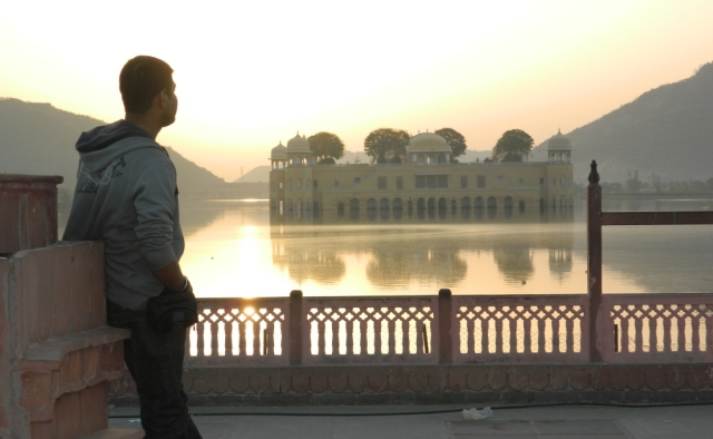 arjun looking over a flat lake to a palace in the indian sunshine