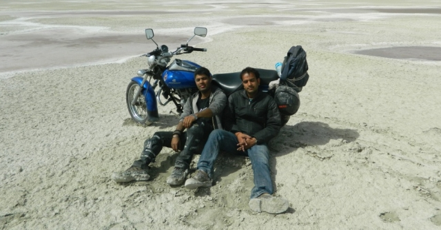 arjun and friend relaxing next to a bike on the salt lake