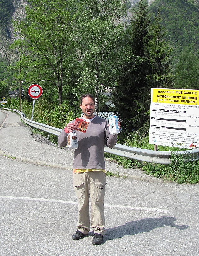 the bf holding boxes and bags with breakfast foods by the trees and roads into le bourg d'oisans