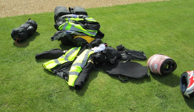 bike jackets, pants and luggage on the grass at the campsite in cambridge