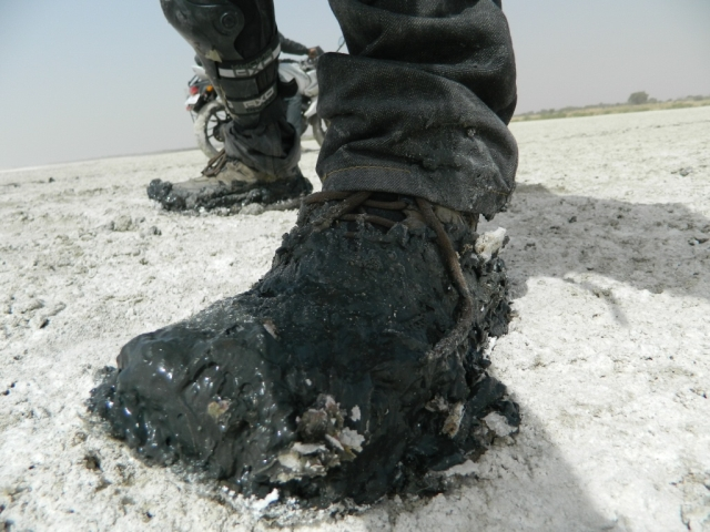 boots covered in black salty mud