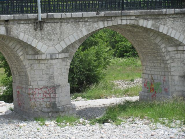 old stone built bridge over dry river bad with some graffiti under the arches