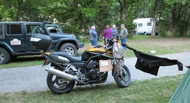 my motorcycle next to the tent with clothes drying on a cord between them. big 4 by 4 behind and people talking