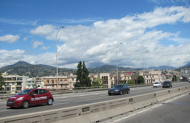 a sunny dual carriageway with a large town below which is Nice on the Cote D'Azur
