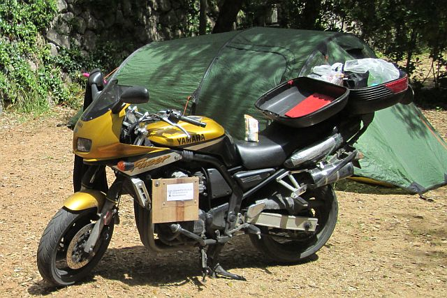 yamaha fzs 600 in the sunshine next to a tent at a campsite on the french riviera