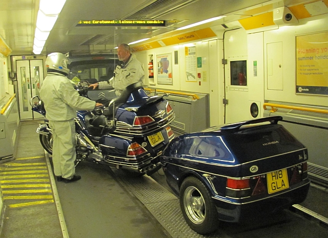 a honda gold wing with riders and trailer in the channel tunnel train
