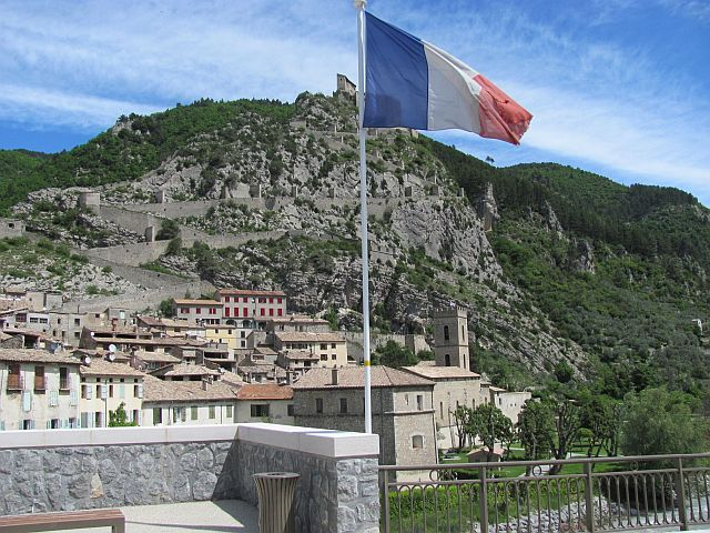 a rocky hillside with a town clinging to the slopes, a french flag in the foreground