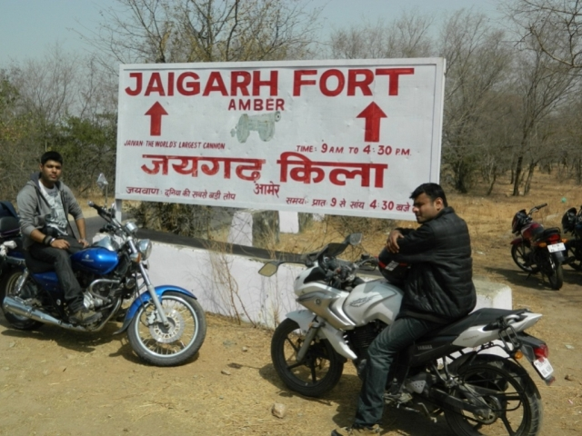 arjun and friend posing by the jaigarh fort sign