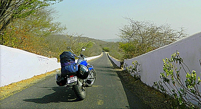 a loaded motorcycle on a long narrow coutryside lane in india