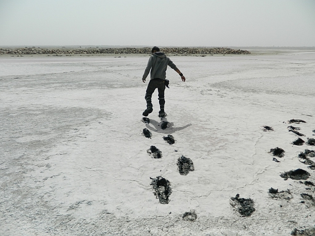 man walking through the muddy sambhar salt lake