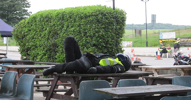 A very tired motorcyclist still wearing his bike gear and helmet sleeps on a table