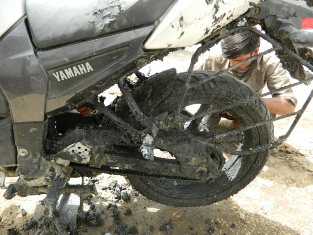 motorcycle covered in thick salt mud