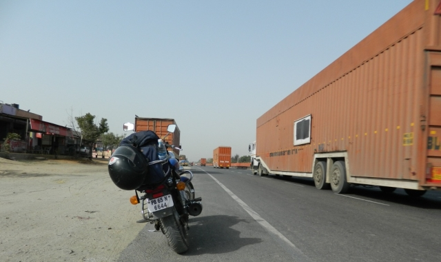 large trucks whizz past a parked motorcycle in the terrifying indian roads