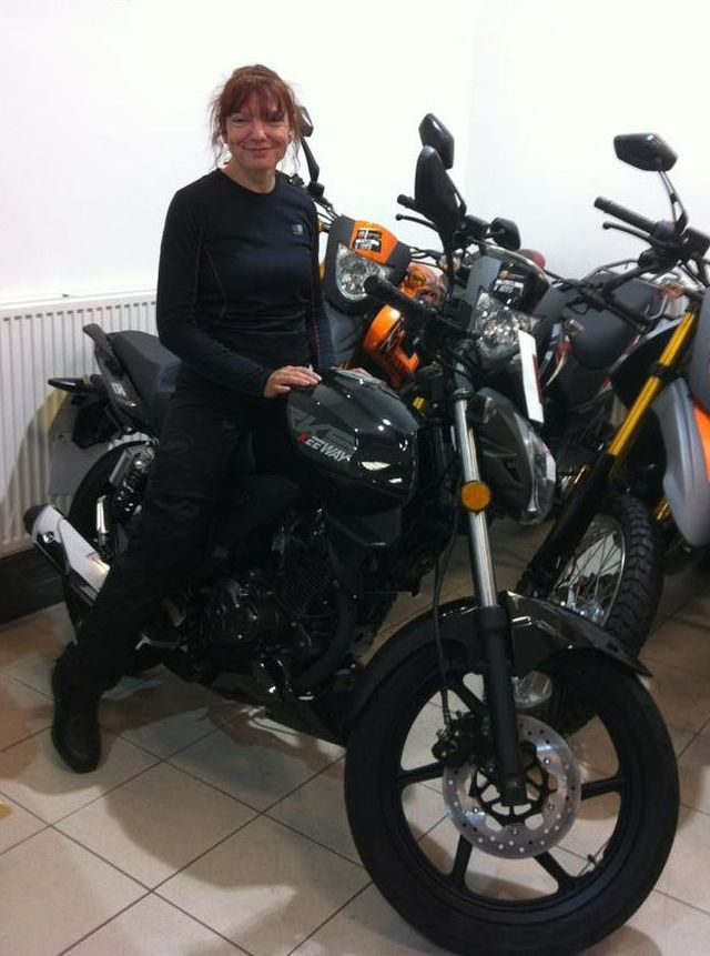 Sharon sits smiling on her new Keeway RKS125 in the shops