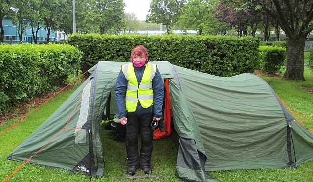 Sharon outside a tent swaddled deep in waterproofs on a wet and windy day