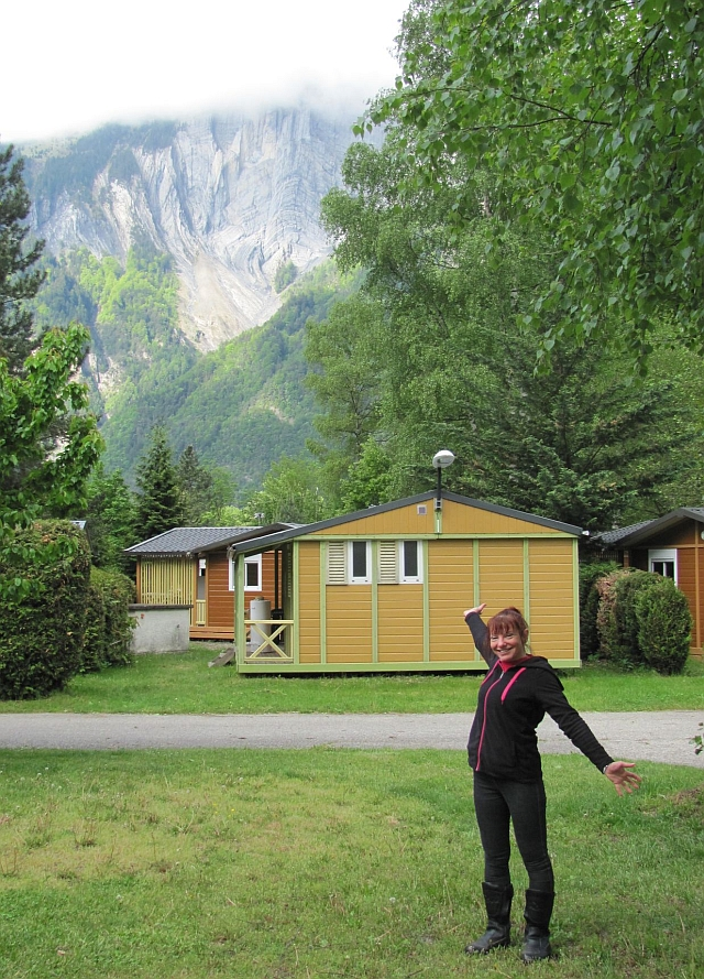 sharon in her thermal undies pointing to the steep mountins sides in le bourg d'oisans in the Alps