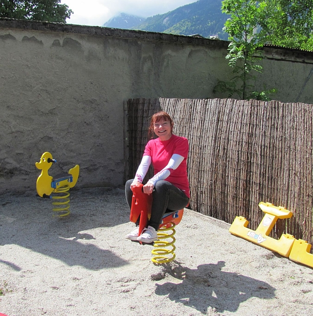 sharon on the spring mounted wooden horse smiling and beaming at la piscine campsite bourg d'oisans