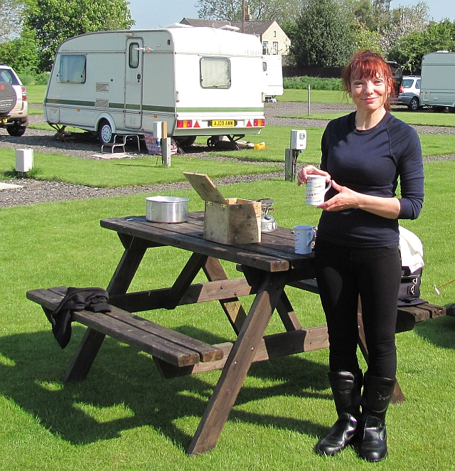 Sharon with a cup of tea in the sun at the campsite in cambridge